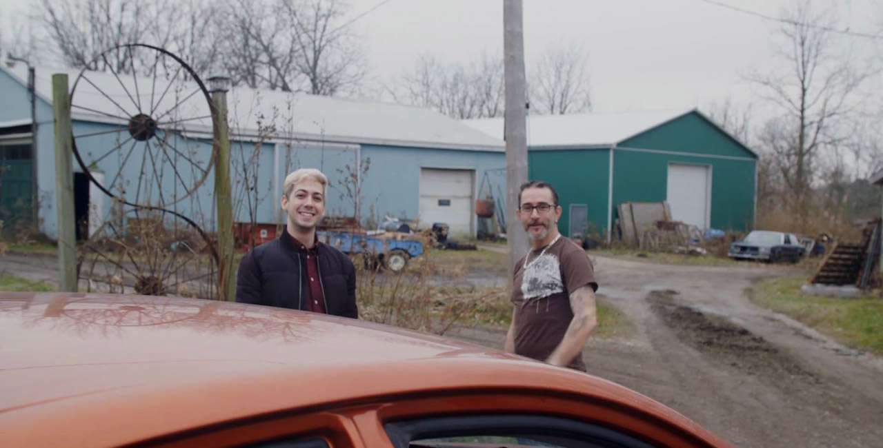 Two men smile for the camera by a car