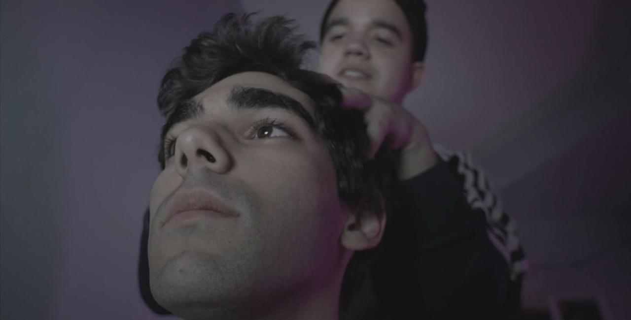A man scratches another man's head