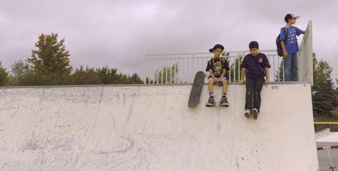 three kids sit on a skateboard halfpipe