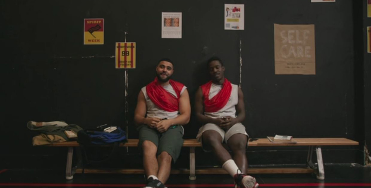 Two men sit on a bench in a changeroom