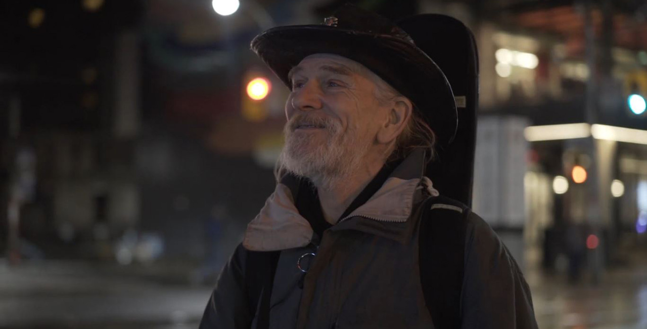 A man in a cowboy hat stands on the streets of Toronto